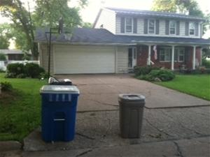 Recycling and trash bin in front of house